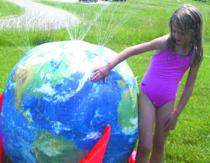 Julia Hydeb cools off at a globe at the kickoff. The theme of the summer reading program is &quot;One World, Many Stories.&quot;