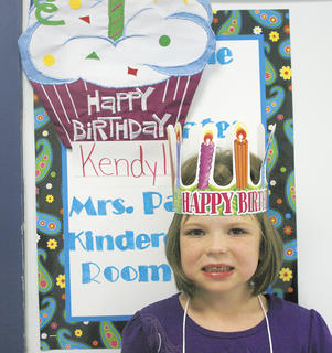 Kendyl Patrick smiles in front of a sign in observance of her birthday. She is a student at Crittenden-Mt. Zion Elementary.