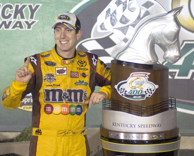 "Kyle Busch poses next to his trophy, after winning the inaugural ""Quaker State 400"" July 9 at the Kentucky Speedway."