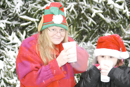 Laura Golden of Crittenden and her granddaughter, Brielle Evans, warm up with hot chocolate while waiting for the Christmas parade to begin.