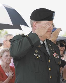 Lt. Col. Jim Simpson salutes during the singing of the National Anthem. He delivered the invocation and the benediction.