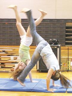 Mary Brinker and Emily Houk perform gymnastic routines for the crowd.