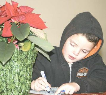Michael Frazure works a word puzzle at the Dry Ridge Baptist Church SNAC Christmas party at Meadow View.
