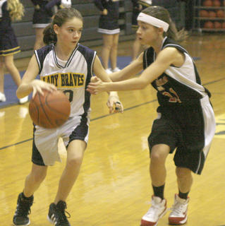 Sixth grader Kendall Clemons drives the lane against the Conner defender.