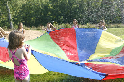 Kids hold tight as water bounces off their parachute.