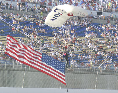 A paratrooper lands on the midfield during pre-race ceremonies.