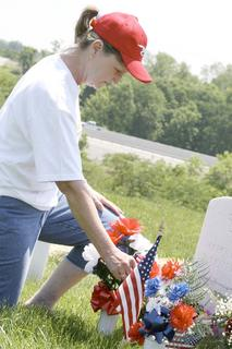 "Patricia Mann, of Dry Ridge, places flowers on the grave of her brother, Harold ""Butch"" Covey."
