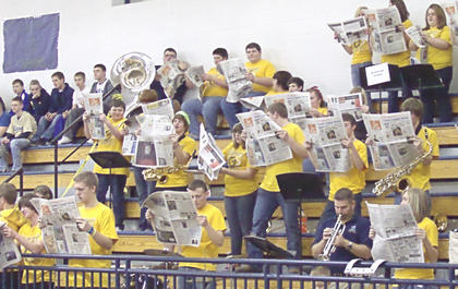 The pep band gets into the spirit of reading the paper as the opposing team is introduced. 