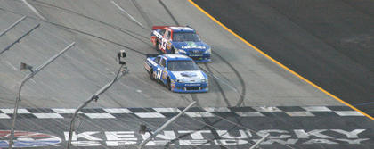 "Andy Lally (71) passes Casey Mears (13) during the ""Quaker State 400"" July 9 at the Kentucky Speedway. Lally finished 32nd and Mears finished 25th in the race."