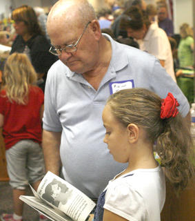 Blaine Turner looks at the book his granddaughter Rebekah Turner is skimming through at the book fair.