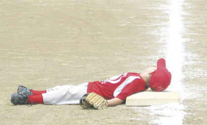 The third baseman takes a nap during a t-ball game.
