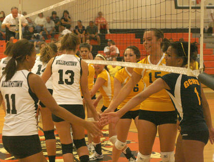 Lady Demons and Lady Braves greet each other at the net prior to the start of the game Sept. 1.