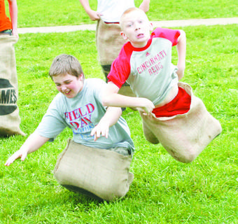 Jason Eilers and Dawson Cannon show their competitive spirit during CMZ's track and field day sack race.