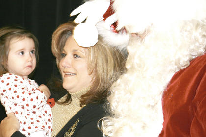 Shelby McCandless, 2, cautiously looks at Santa Claus, with her grandmother during Santa&#039;s Wonderland in Williamstown.