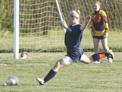Lady Braves' Kelsey Lund builds a big stride before kicking the ball forward.