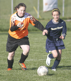 Olivia Souder, left, and Faith Johnson, right, struggle for control of the ball in the first half.