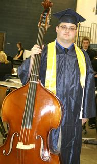 Trent Wilson prepares to play his bass for a final concert during graduation ceremonies.