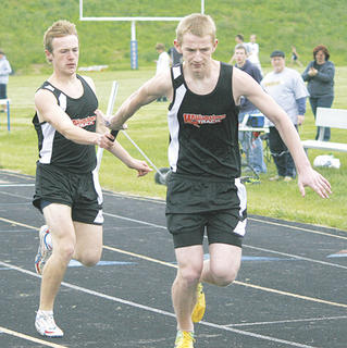 Williamstown High School freshman Anthony Cook hands the baton to senior William May during the 4x200 meter relay.