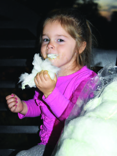 Ellie Bush gets a big mouthful of cotton candy.