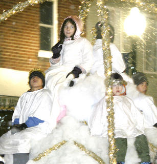 A group of angels participate in the Christmas parade.