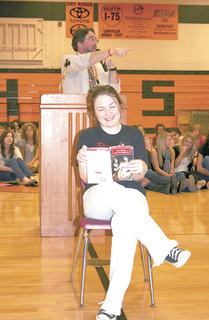 Brittany Hoskins isn't fazed by the bidding as she keeps on reading.
