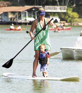 Brayden Kenner goes along for a ride on a paddleboard navigated by his mother, Ashlee Kenner.