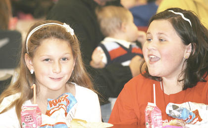 Best friends Mary Brinker, 9, and Courtney Nunnelley, 10, enjoy their lunch with Santa at WHS.