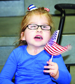 DRE kindergartner Cale Meade waves her flag.  Photos by Bryan Marshall, Camille McClanahan, Amanda Kelly, Linda Lawrence and Mark Verbeck.