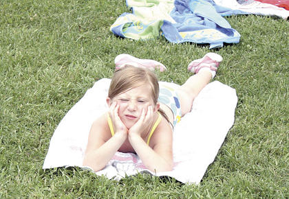 Morgan Bigelow patiently waits for the pools and slide to be ready while soaking in the sun.