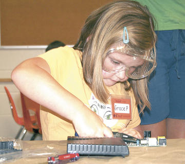 Grace Porter concentrates as she works on her project at Camp Invention.
