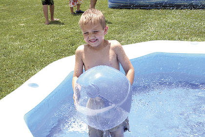 Isaiah Hanson plays with a beach ball in the pool.