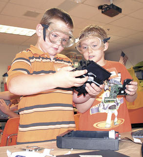 Tyler Kinman, left, and Logan Carmichael, right, discuss a part removed from a CD player and how they can partner up at Camp Invention at WES.