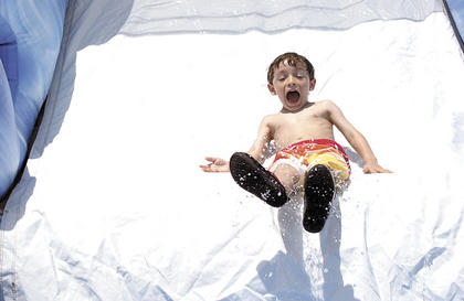 Aiden Palmer gets some air on his way down the slide at Little Dippers Camp.