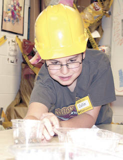 Collin Davis checks on an experiment his group works on during Camp invention.