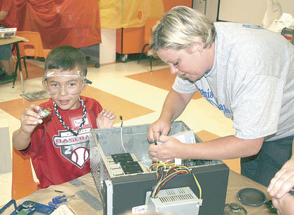 "Tucker Gray shows off a part he removed from an old computer in th e""I Can Invent: Edison's Workshop"" room at Camp Invention at Williamstown Elementary School with help from Sarah Marksbury."
