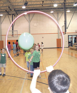 Brooklyn Hammons throws a perfect shot through a hula hoop in a game activity during camp.