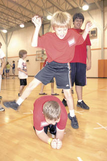 Evan Dunaway leap frogs over a fellow camper during a game in the WES gym.