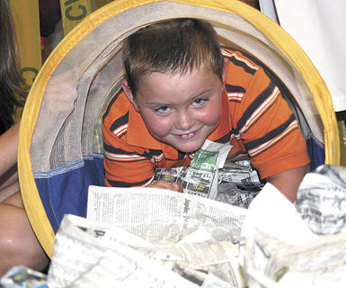 Tyler Kinman crawls through a trash filled tunnel into the &quot;Saving Sludge City&quot; classroom at Camp Invention at Williamstown Elementary School.