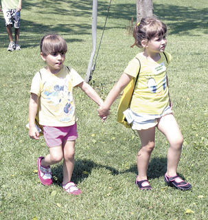 Nevaeh Rowe and Abby Knarr hold hands as they walk to their next activity.