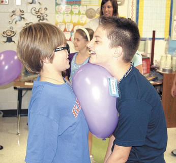Nicholas Day, left, and Tanner Dalton, right, try to keep a balloon afloat during Camp Invention at WES.