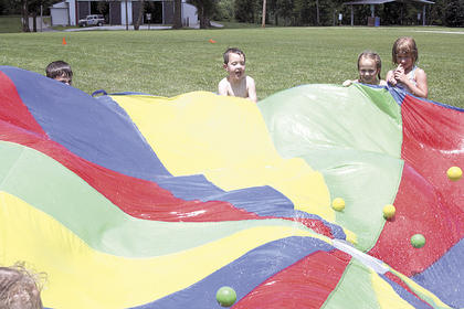 Connor Whaley, MaKenah McKenney and Haley Saddler try to get plastic balls in the air by shaking a wet, rainbow-colored tarp.