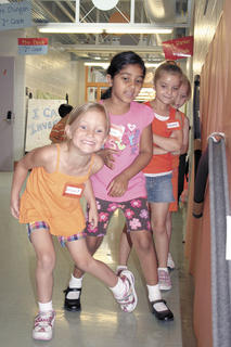 From left, Grace Fields, Shayna Bassi, Eleanor Schultz and Shelby Marksbury watch as a marble goes down a rollercoaster they designed and built with tubing at Camp Invention.