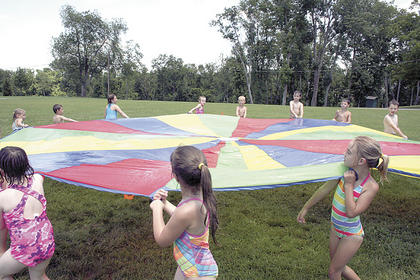 Campers spin the parachute tarp in a circle.