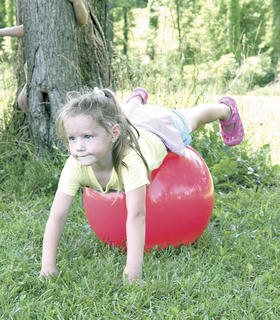 Katrina Cooper takes a ride on a bouncy ball.