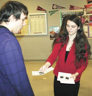 GCHS student Brittnie Seibert hands out brochures at the mock debate.