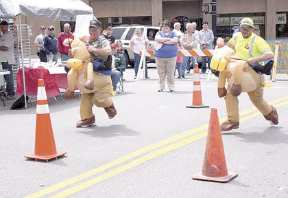 Chris Webster of the GC Road Dept. and James Rayburn of the state road dept, compete in the celebrity horse race.