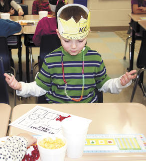 SES student Brennen Farmer counts 10 sets of 10 different snacks, on a 100th day project.