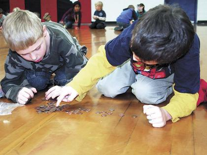 Wesley Noel and Derick Floyd, first grade students at Dry Ridge Elementary, count pennies as part of a penny war for the DRE Relay For Life team.