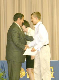 Seth Adkins recieves his diploma from principal Tim Grayson.