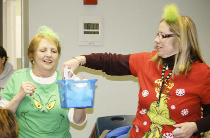 Grant County librarian Susan Nimersheim pulls a name for a drawing during The Grinch party.